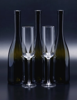 Tre bottiglie di vino e due bicchieri di vino vuoti