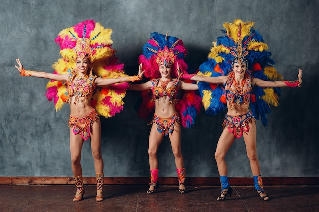 Tre donne in costume di carnevale samba brasiliana con piumaggio di piume colorate.