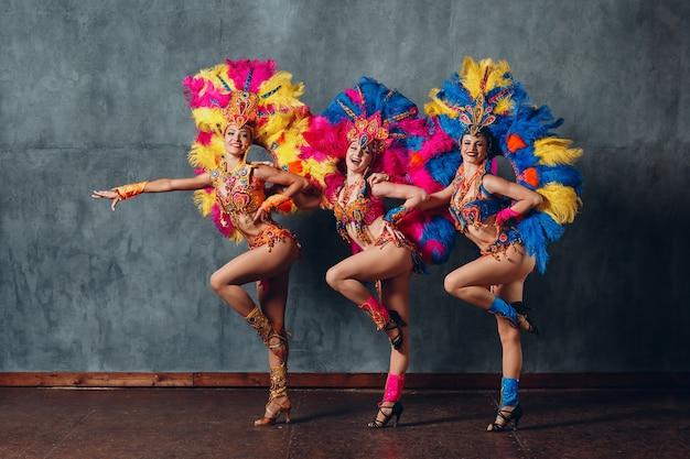 Tre donne in costume da cabaret con piumaggio di piume colorate.