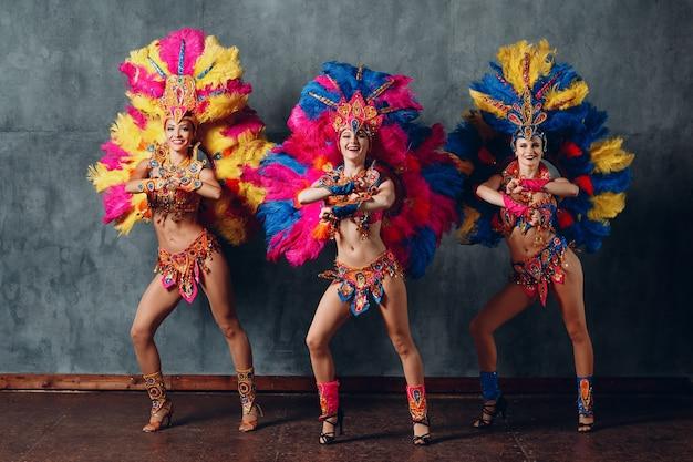Tre donne che ballano in costume di carnevale samba brasiliano con piume colorate.