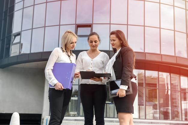 Informazioni di lettura di tre donne nella cartella. stanno in piedi fuori dall'edificio degli uffici e vestiti in giacca e cravatta