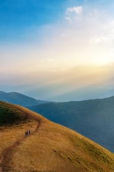 Tre donne che trekking su un'alta montagna con una priorità bassa scenica e blu del cielo di bella natura