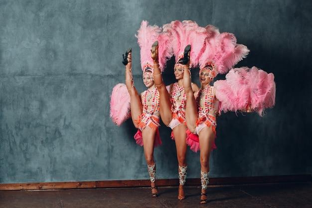 Tre donne in costume da cabaret con piumaggio di piume rosa.