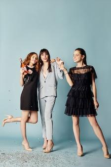 Tre donne festeggiano la festa divertendosi ridendo e mangiando torte sotto i coriandoli volanti