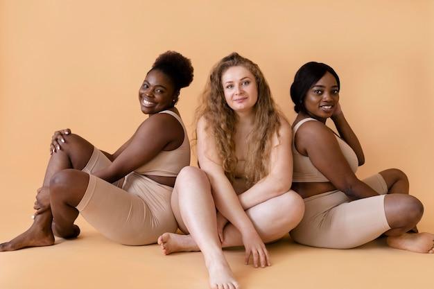 Tre donne in shapers del corpo nudo che propongono insieme