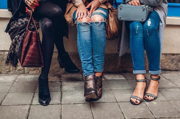 Tre donne che indossano scarpe alla moda, abbigliamento e accessori all'aperto. concetto di moda di bellezza.