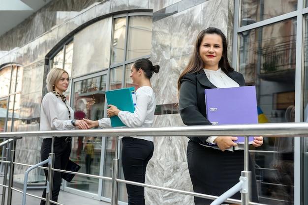 Tre donne con cartelle in piedi fuori dall'edificio e che guardano nei documenti