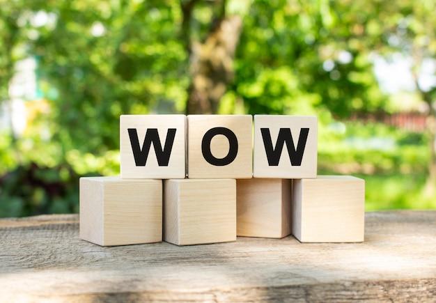 Tre cubi di legno sono impilati nella parola wow. si trovano su altri cubi sullo sfondo del giardino estivo.