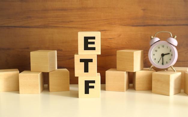 Tre cubi di legno impilati verticalmente su uno sfondo marrone compongono la parola etf. i cubi sono sparsi nelle vicinanze e c'è un orologio. concetti vista frontale front