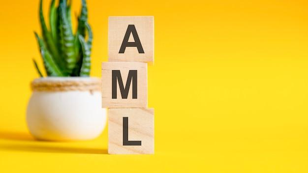 Tre cubi di legno con lettere - aml, sul tavolo giallo, spazio per il testo a destra. aml - abbreviazione di antiriciclaggio. concetti vista frontale, fiore sullo sfondo