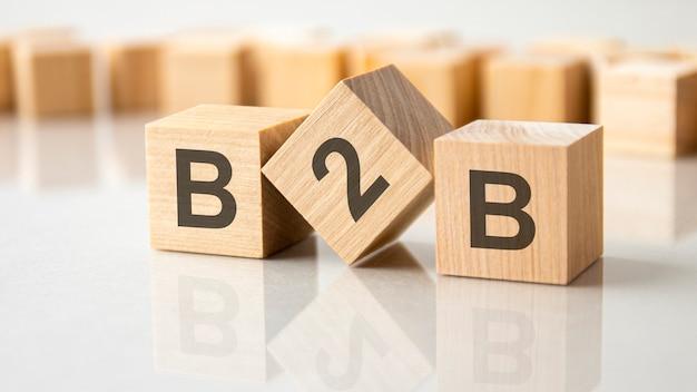 Tre cubi di legno con le lettere b2b sulla superficie luminosa di un tavolo grigio, concetto di business