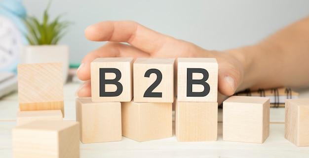 Tre cubi di legno con lettere b2b, sul tavolo bianco, più in background, spazio per il testo nell'angolo in basso a destra