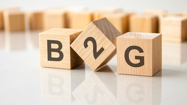 Tre cubi di legno con le lettere b2g sulla superficie luminosa di un tavolo grigio. l'iscrizione sui cubi è riflessa dalla superficie del tavolo. b2g - abbreviazione di business to government