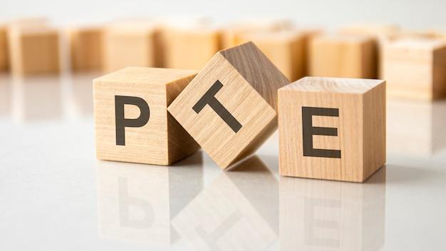 Tre cubi di legno con le lettere pte sulla superficie luminosa di un tavolo grigio. l'iscrizione sui cubi è riflessa dalla superficie del tavolo. pte - abbreviazione di pearson test of english