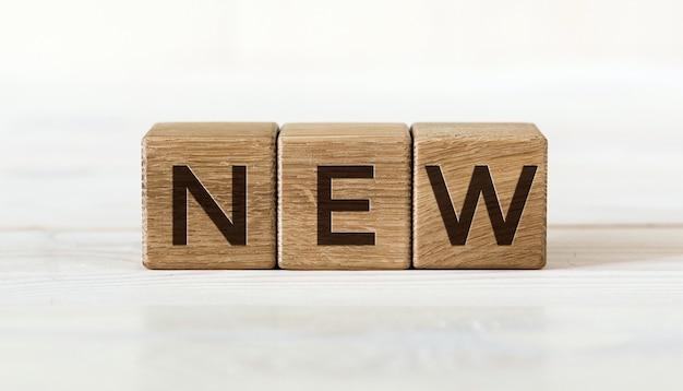 Tre cubi di legno con la parola nuovo, su sfondo bianco.