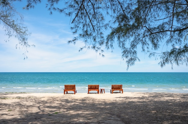 Tre lounge in legno sulla spiaggia in mare tropicale in estate