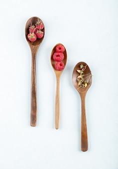Tre cucchiai di legno di lamponi rossi e foglie secche su una superficie in pietra