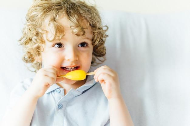 Ragazzo biondo di tre anni con riccioli sorridente seduto sul divano di casa a mangiare un gelato sorridente con spazio per la copia. bambini gelato e concetto estivo