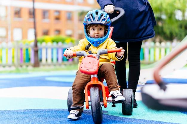 Bambino di tre anni in sella a un triciclo con un casco in un parco