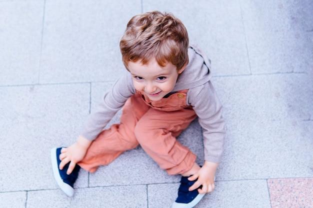 Bambino di tre anni seduto per terra in strada con uno sguardo e un gesto malizioso