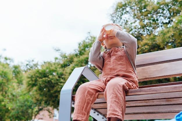 Bambino di tre anni che affetta una vaschetta di gelato con la bocca per strada con sua madre