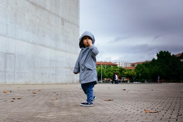 Bambino di tre anni per strada in autunno con il cappotto in una giornata nuvolosa