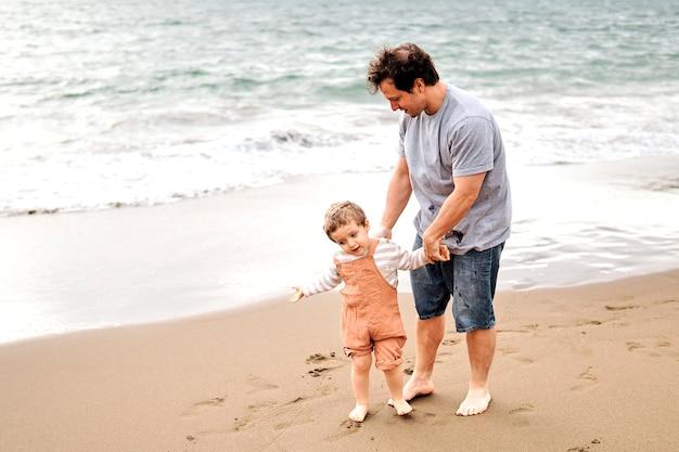 Bambino di tre anni che cerca di convincere suo padre che vuole fare il bagno in mare