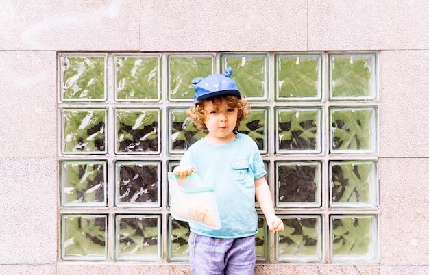 Bambino di tre anni con un berretto blu che fa merenda per strada