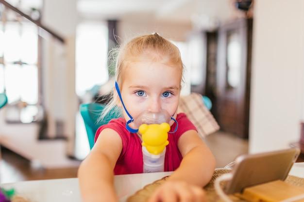 Bambino di tre anni con asma allergico, inalando le sue medicine attraverso il distanziatore dei bambini mentre guardava con gli occhi stanchi.