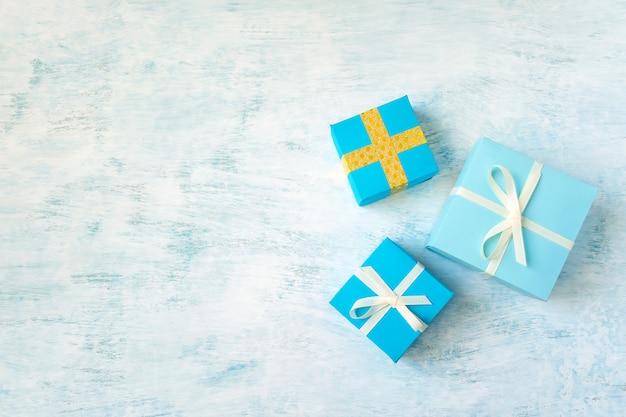 Tre scatola regalo giallo e blu su sfondo pastello blu chiaro