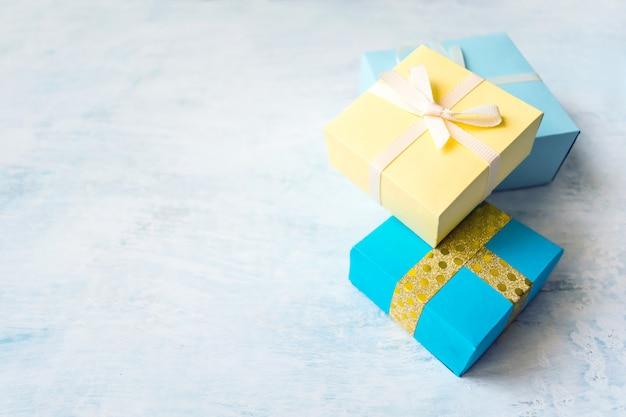 Tre scatola regalo giallo e blu su sfondo pastello