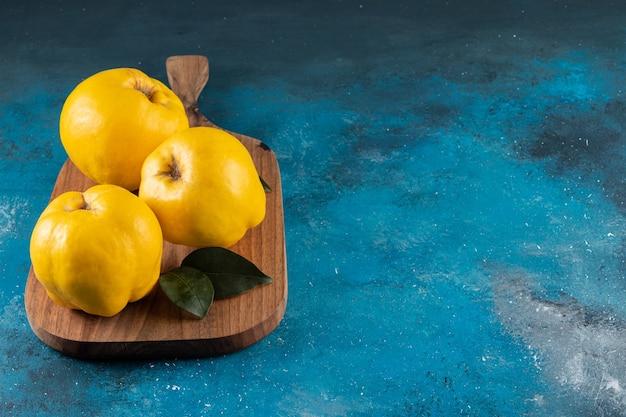 Tre frutti di mela cotogna gialli posti sulla tavola di legno