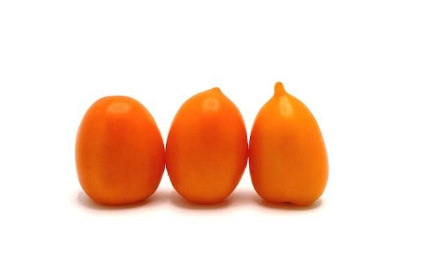 Tre pomodori maturi gialli su sfondo chiaro. prodotto naturale. colore naturale. avvicinamento.