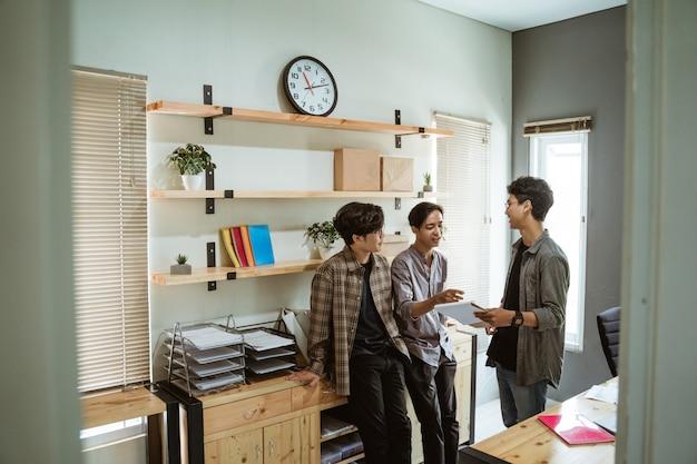 Tre giovani uomo d'affari asiatico in chat sul loro prodotto