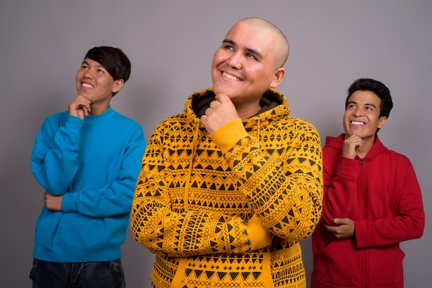 Tre giovani uomini asiatici che indossano abiti caldi contro il muro grigio