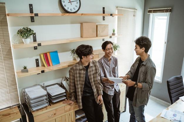 Tre giovani lavoratori asiatici in chat sul loro prodotto