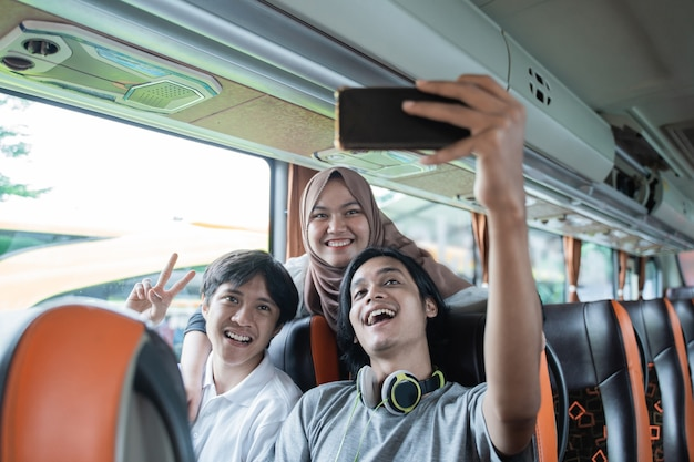 Tre giovani asiatici sorridono e posano davanti alla fotocamera del cellulare mentre si fanno un selfie insieme sull'autobus