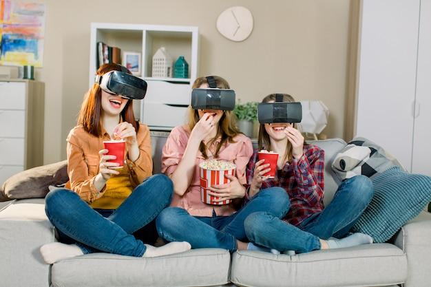 Tre giovani donne attraenti che indossano gli occhiali per la visione della realtà virtuale della cuffia avricolare che guardano video, che si siedono sul sofà e che mangiano il popcorn nella stanza accogliente