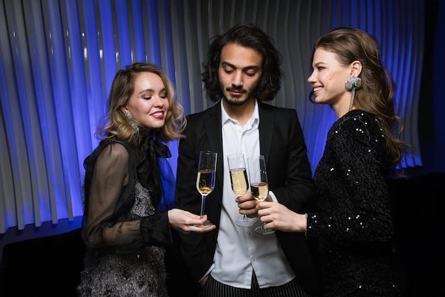 Tre giovani amici eleganti allietare con flauti di champagne alla festa durante la celebrazione nel night club