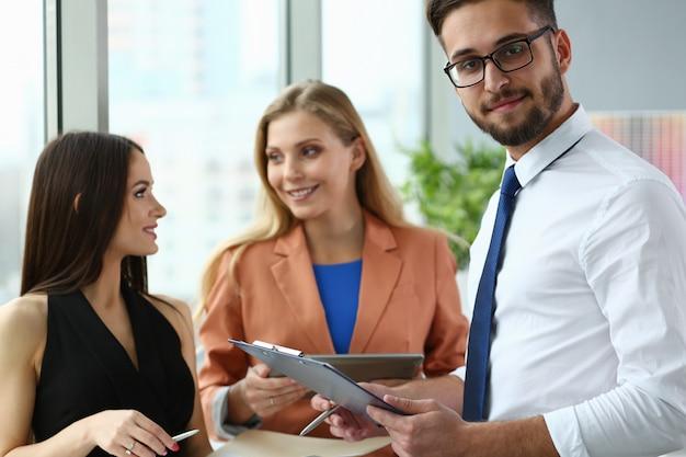 Tre giovani impiegati in chat in ufficio