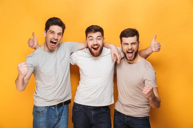 Tre giovani uomini eccitati che mostrano i pollici in su