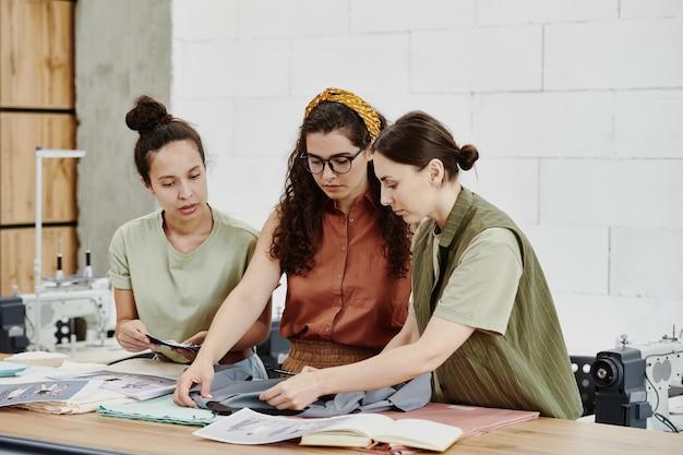 Tre giovani stilisti in piedi a tavola in officina e scegliendo il tessuto per uno degli articoli della collezione stagionale
