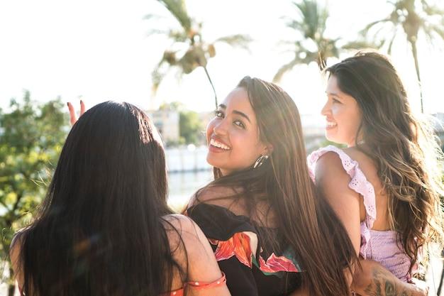 Tre giovani amici all'aperto si godono un bel pomeriggio estivo ragazze latine sedute insieme