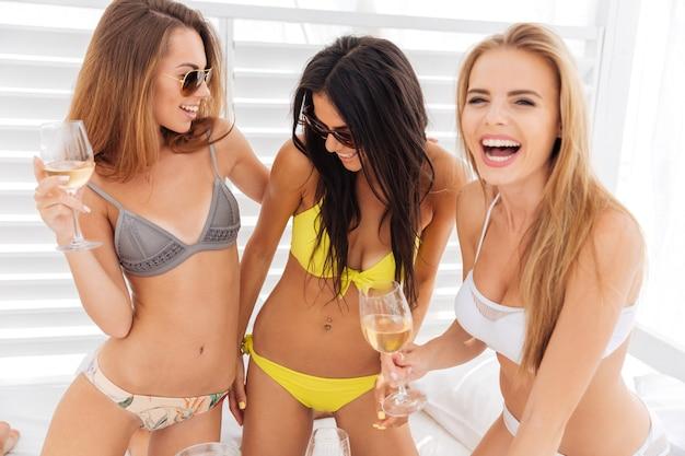 Tre giovani belle ragazze felici in bikini che bevono e si divertono all'aperto