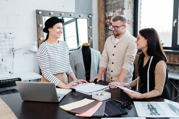 Tre giovani designer felici che discutono di nuovi modelli di moda per la collezione stagionale mentre lavorano