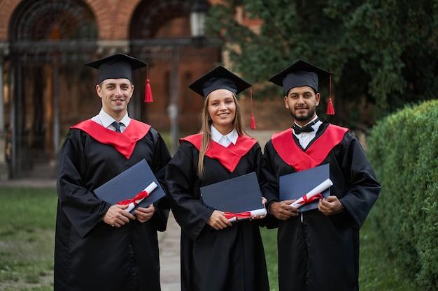Tre giovani laureati felici provenienti da diversi paesi con diplomi in mano e in abiti da laurea