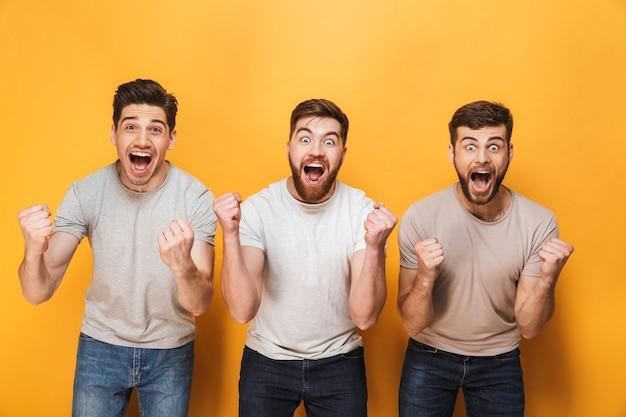 Tre giovani uomini felici che celebrano insieme il successo