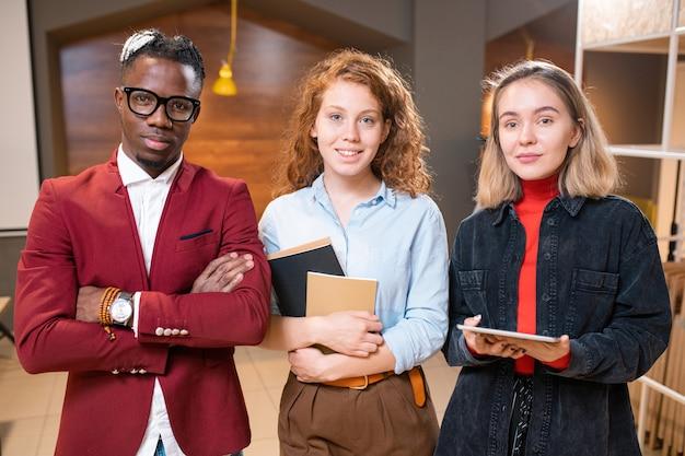 Tre giovani amici del college interculturale o compagni di gruppo in abbigliamento casual nella caffetteria