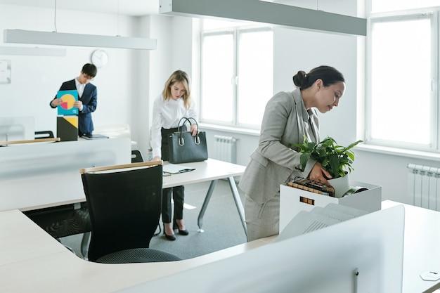 Tre giovani direttori d'ufficio interculturali che tornano sui luoghi di lavoro, stanno in piedi alle loro scrivanie e posano carte e provviste