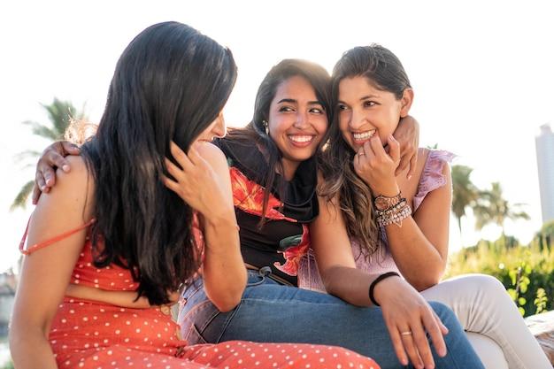 Tre giovani amiche latine che conversano all'aperto in una soleggiata giornata estiva